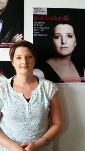 OLT, Laure vor Plakat Würdenträgerin
